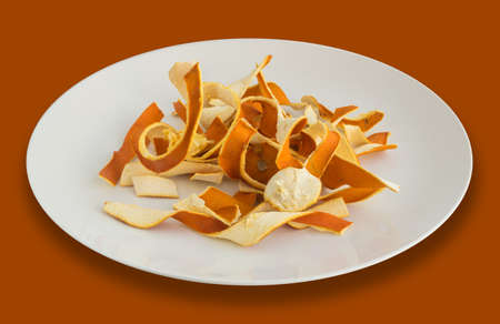 Dry Orange Peel in White Plate. Zest Photographed with Natural Light Top View
