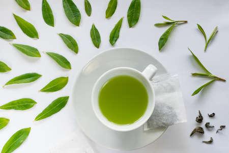Tazza di tè verde chiaro sano con la disposizione piana delle foglie verdi fresche Archivio Fotografico - 81620644