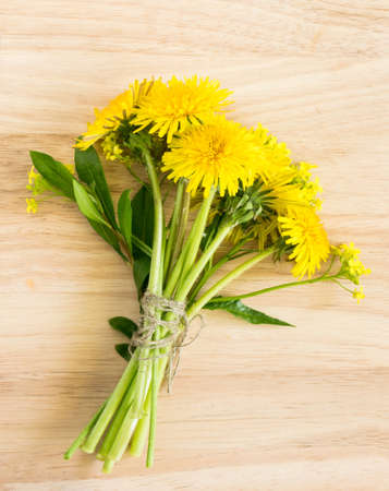 Bouquet of Dandelion Flowers on Wooden Background. Beautiful Yellow Blossoms Close Up