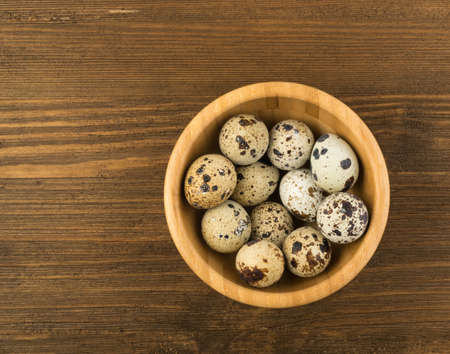 Quail Eggs in Wooden Bowl Top View. Small Whole Eggs with Place for Text