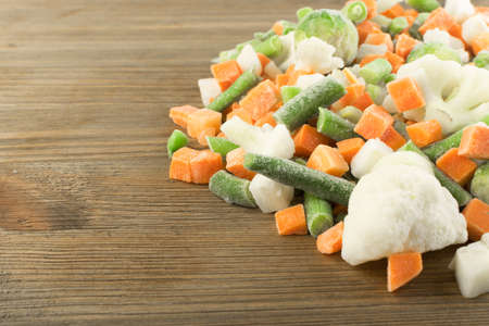 Frozen Mixed Vegetables on Wooden Background. Raw Chopped Carrot, Cauliflower, Onion, Green Beans and Brussels Sprouts Stock Photo