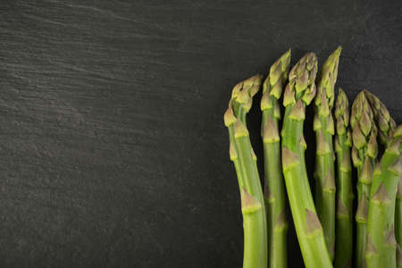 Bunch of Raw Garden Asparagus Top View. Fresh Green Spring Vegetables on Natural Stone Background with Space for Text.