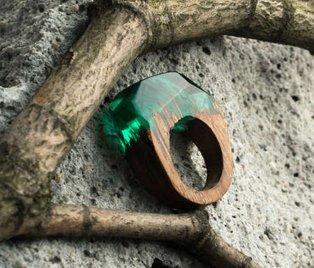 Green Ring Made of Wood and Resin. Handmade Bijouterie on Natural Wood Background