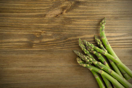Bunch of Raw Garden Asparagus Top View. Fresh Green Spring Vegetables on Wooden Background with Space for Text.