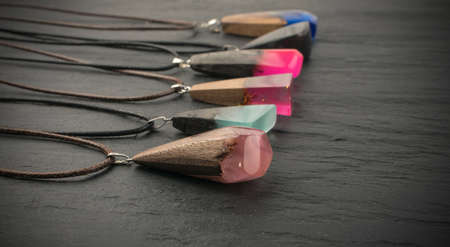 Different Pendants of Pink, Blue and Green Color on Black Stone Background. Bijouterie Made of Epoxy Resin and Wood 스톡 콘텐츠