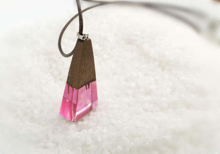 Hand Made Pink Wood Pendant on White Crystal Background. Author Creative Bijouterie Made of Epoxy Resin and Wood