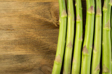 Raw Garden Asparagus Stems Top View. Fresh Green Spring Vegetables on Wooden Background with Space for Text.