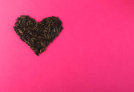 Raw Black Wild Rice Heart on Pink Paper Background Top View. Healthy Dietetic Canada Rice Cereal with Place for Text 스톡 콘텐츠