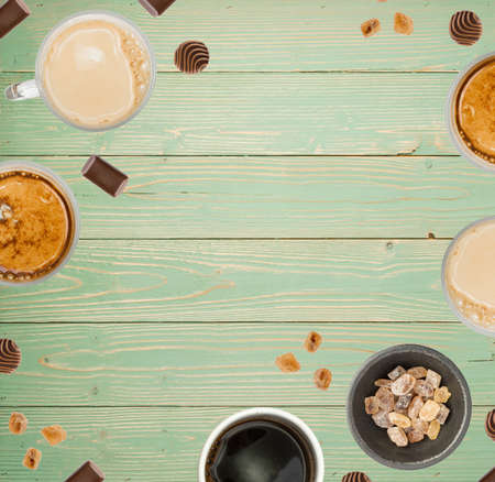 Creative Food Pattern with Coffee Cups on Turquoise Wood Background Top View. Hot Beverages Layout with Copyspace