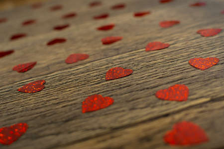 Red Glittering Heart Confetti on Old Rustic Wood Background Top View. Romance Gift Texture on Vintage Weathered Wooden Table as Holiday, Hope and Love Concept, Pattern, Backdrop Banque d'images