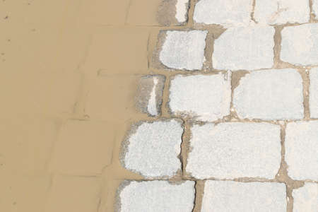 Grey Old Pavement with a a Dirty Puddle after the Rain Top View or Granite Cobblestone Road. Ancient Brick Cobblestoned Floor or Granite Tiles Street with Big Stones