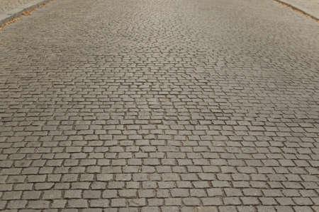Graue alte Pflaster-Draufsicht oder Granit-Kopfsteinpflasterstraße. Alter Ziegelsteinpflasterboden oder Granitfliesenstraße mit großen Steinen