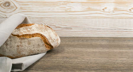 Homemade Freshly Baked Traditional Bread on Dark Wooden Table Top View with Copyspace. Whole Loaf of Rustic Italian Cereal Bread Made of Sourdough Dough with Space for Text