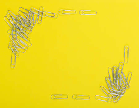Frame of note paper clips on yellow background top view. Pile of steel clips or paperclips close up Reklamní fotografie