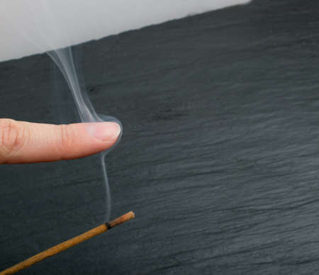 Burning indian incense spa aroma stick with smoke on black stone background. Fragrant scented smoky sandalwood sticks for aromatherapy