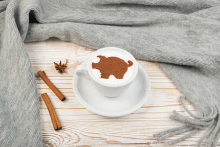 Macchiato or Latte Cappuccino on Rustic Wooden Background with 2019 New Year Pig Symbol. Holiday Mockup with Hot Coffee Cup and Piggy Silhouette on Cream Milk Foam Stock Photo