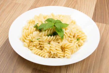 Fusilli Spirale Pasta Al Dente with Parmigiano Reggiano Cheese, Spices and Basil in Restaurant Plate Close Up. Traditional Italian Macaroni with Parmesan