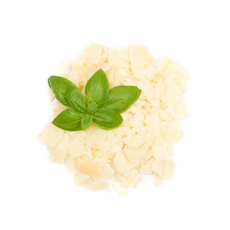 Pile of parmesan cheese flakes and crumbs with basil leaves isolated on white background. Square pieces of Italian parmigiano reggiano for salads and pasta close up