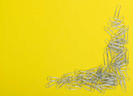 Heap of note paper clips on yellow background top view. Pile of steel clips or paperclips