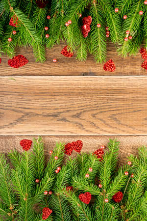Christmas background with fir branches on wooden backdrop flat lay and top view. Yuletide floral frame decoration with  space. Creative xmas tree border for New Year greeting card Zdjęcie Seryjne
