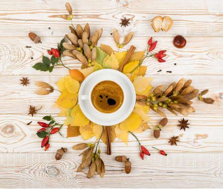 Floral autumn background with a mug of coffee surrounded by leaves, autumn tree seeds and fragrant spices. Hot drink composition on rustic wooden table background Stock Photo