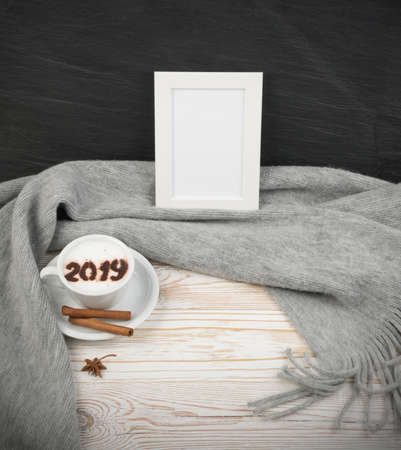 2019 Macchiato or Latte Cappuccino on Rustic Wooden Background with Grey Plaid. Hot Coffee Cup with Cream Milk Foam on Wood Table