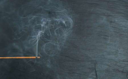 Burning indian incense aroma sticks with smoke on black stone background. Fragrant smoky sandalwood stick top view Фото со стока - 111879746