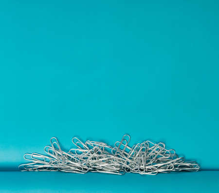 Heap of note paper clips on blue background top view. Pile of steel clips or paperclips with Stock Photo