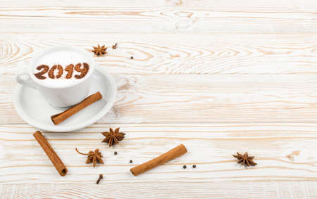 New Year Numbers 2019 on Macchiato or Latte Cappuccino on Rustic Wooden Background. Hot Coffee Cup with Cream Milk Foam and Picture on a Festive Theme