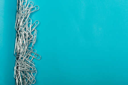 Heap of note paper clips on blue background top view. Pile of steel clips or paperclips with copyspace