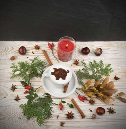 Macchiato or Latte Cappuccino on Rustic Wooden Background with 2019 New Year Pig Symbol and Aromatic Spices. Holiday Mockup with Hot Coffee Cup and Piggy Silhouette on Cream Milk Foam