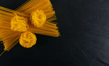 Raw yellow italian pasta fettuccine, fettuccelle or tagliatelle close up. Egg homemade dry ribbon noodles, long rolled macaroni or uncooked spaghetti on black stone background top view