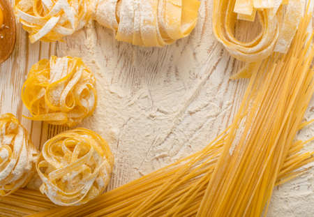 Raw yellow italian pasta pappardelle, fettuccine or tagliatelle on wooden background close up. Egg homemade noodles cooking process, long rolled macaroni, uncooked spaghetti with place for text