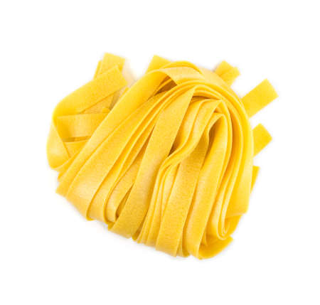 Raw yellow italian pasta pappardelle, fettuccine or tagliatelle close up. Egg homemade dry ribbon noodles, long rolled macaroni or uncooked spaghetti isolated top view Stockfoto