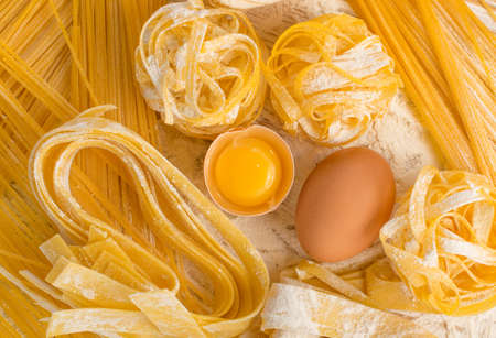 Raw yellow italian pasta pappardelle, fettuccine or tagliatelle close up with eggs. Egg homemade noodles cooking process, long rolled macaroni, uncooked spaghetti top view