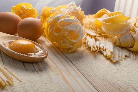 Raw yellow italian pasta pappardelle, fettuccine or tagliatelle close up with eggs. Egg homemade noodles cooking process with long macaroni or spaghetti against flour background with place for text