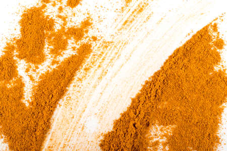 Smeared Mixture of Indian Spices and Herbs Powders with Cumin, Curry, Curcuma, Turmeric and Chilli Pepper. Orange Seasoning Powder Texture on White Background Top View Stock Photo