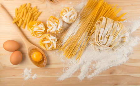 Raw yellow italian pasta pappardelle, fettuccine or tagliatelle close up with eggs. Egg homemade noodles cooking process, long rolled macaroni or uncooked spaghetti on wood table