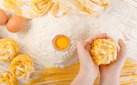 Child hand holding raw yellow italian pasta pappardelle, fettuccine or tagliatelle close up with eggs. Egg noodles cooking process, long rolled macaroni or uncooked spaghetti against flour background Stockfoto