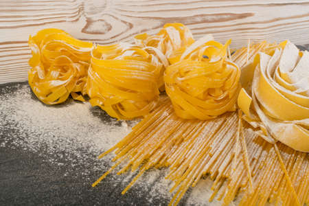 Raw yellow italian pasta pappardelle, fettuccine or tagliatelle close up. Egg homemade noodles cooking process, long rolled macaroni or uncooked spaghetti