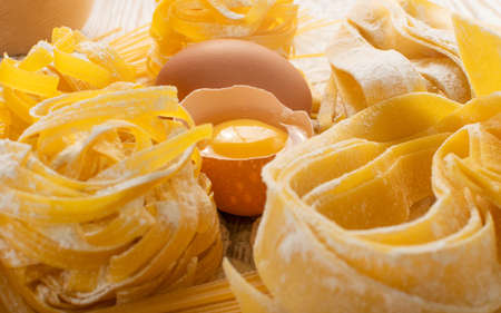 Raw yellow italian pasta pappardelle, fettuccine or tagliatelle close up with eggs. Egg homemade noodles cooking process, long rolled macaroni, uncooked spaghetti
