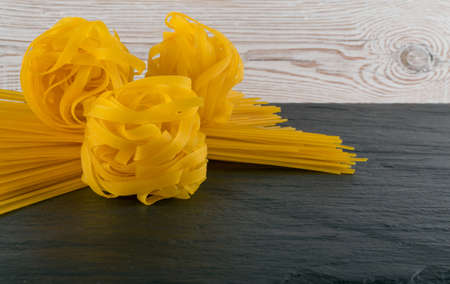 Raw yellow italian pasta fettuccine, fettuccelle or tagliatelle close up. Egg homemade dry ribbon noodles, long rolled macaroni or uncooked spaghetti on black stone background