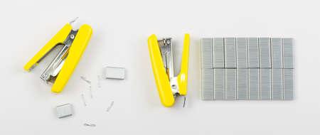 Nueva grapadora de oficina amarilla en el lateral con grapas aisladas sobre fondo blanco Vista superior Foto de archivo