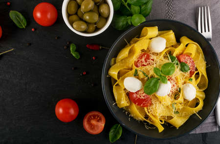 Yellow cooked pasta pappardelle, fettuccine or tagliatelle in black bowl top view. Egg homemade ribbon noodles or macaroni with tomatoes, basil and mozzarella balls on dark rustic background