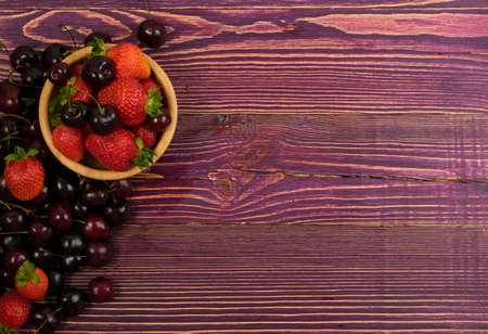 Fresh Summer Strawberries and Cherries on Old Vintage Wooden Background with Copyspace. Burgundy Wood Table Desk Board Texture with Ripe Forest Berries Top View