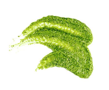 Pesto-Aufstrich oder Klecks auf weißem Hintergrund. Grüne italienische hausgemachte verschüttete Sauce aus gemahlenem Basilikum, Knoblauch, Pinienkernen, Oliven und Pecorino Sardo Käse Draufsicht