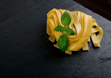 Raw yellow italian pasta pappardelle, fettuccine or tagliatelle close up. Egg homemade dry ribbon noodles, long rolled macaroni or uncooked spaghetti with basil Stockfoto