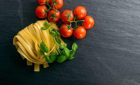 Rohe gelbe italienische Pasta Pappardelle, Fettuccine oder Tagliatelle hautnah. Hausgemachte trockene Bandnudeln mit Ei, lang gerollte Makkaroni oder ungekochte Spaghetti mit Tomaten und Basilikum Draufsicht