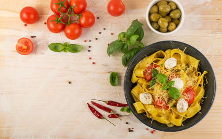 Yellow cooked pasta pappardelle, fettuccine or tagliatelle in black bowl top view. Egg homemade ribbon noodles or macaroni with tomatoes, basil and mozzarella balls on light rustic background