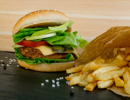 Classic Roast Beef Burger with Fresh Onions, Tomatoes, Green Lettuce Salad, Juicy Cutlet and French Fries. Beefburger with Medium Rare Steak on Black Stone Background